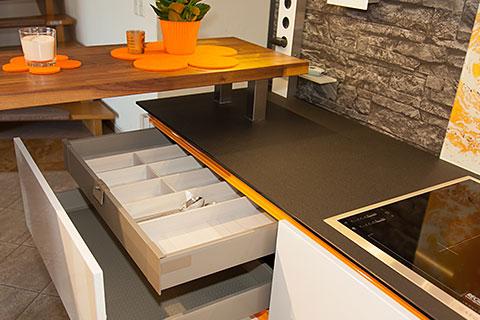 Eine edle weiße lackfront kombiniert mit der frische der orange das sind die zutaten dieser küche selbst die schubkästen mit besteckkasten stören nicht